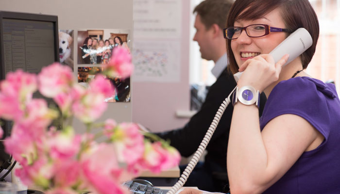 Photo showing member of Cotswold House reception staff answering the phone.