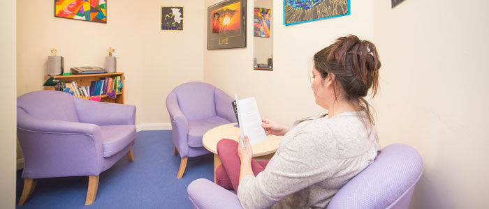 Photo of a Cotswold House patient reading a book