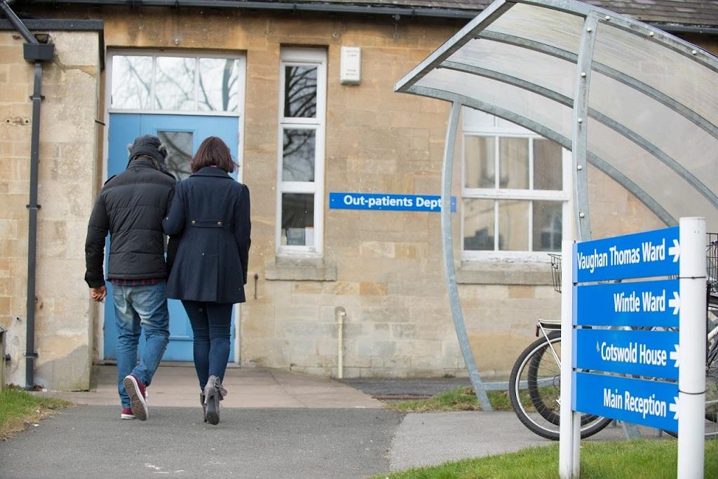 man and woman walking past cycles to ward