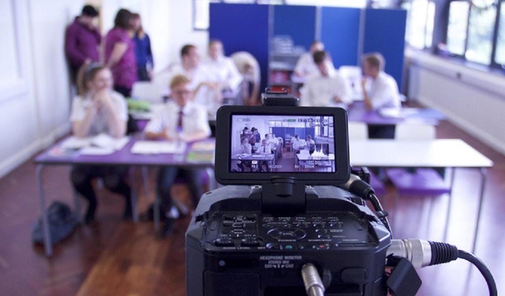 photo of video camera filming young people in conference room