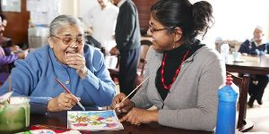 smiling old lady painting with carer
