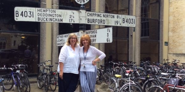 Two women in front of signposts