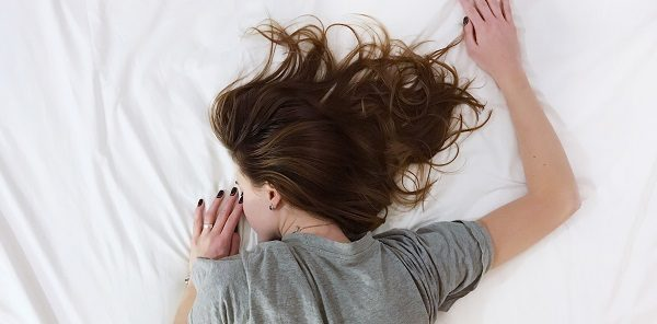 girl lying on her front in bed
