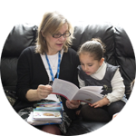 Photo of a child reading a leaflet with a clinician.