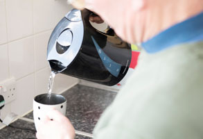 Photo of an older person making a cup of tea.