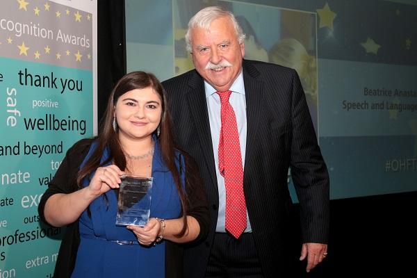 Smiling woman holding an award next to man