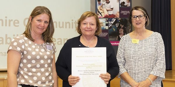 Three smiling women holding up certificate