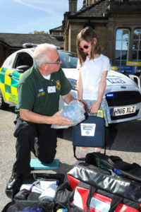 The Oxford Health Charity's Healthfest 2019 at The Warneford Hospital, Oxford.Ambulance Service communinity first responder coordinator Paul Reis explains some of his medical kit to Georgia.