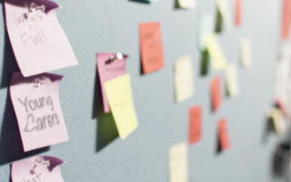 Photo of post-it notes affixed to a pin board.