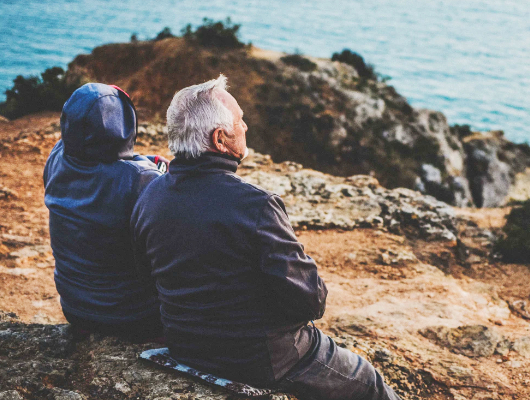 A photo of two older people sitting on a rock and looking out to sea.