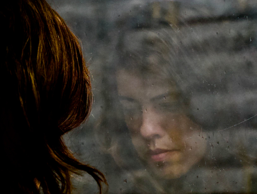 Photo of an unhappy person looking through their window.