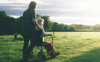 Photo of a carer taking an older relative in a wheelchair for a walk.
