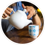 Photo of a person pouring a cup of tea.