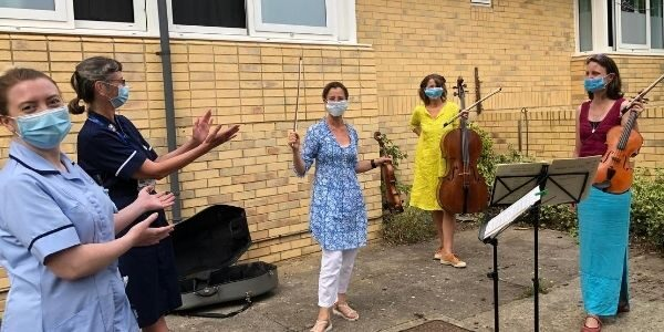 Photo of nurses applauding string trio
