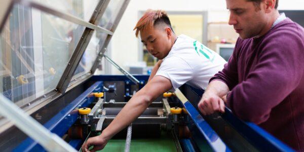 Photo showing engineers maintaining machine at work.