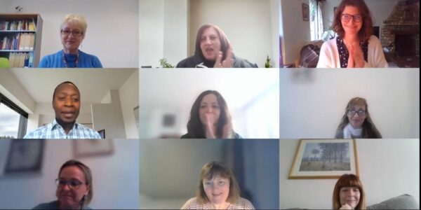 A web meeting showing members of the team clapping and smiling