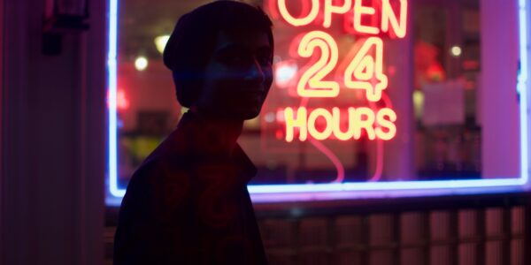 A young man in front of a sign. The sign reads Open 24 hours