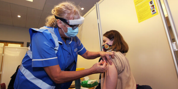 Nurse give NHS worker her covid shot