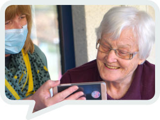 Photo of care worker helping an elderly patient to communicate with her family via a video call.