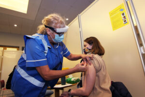 A women being given a covid vaccination by a nurse